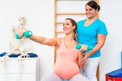 Gravid kvinna som utarbetar med hantlar i sjukgymnastik Arkivfoton