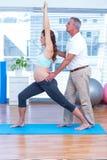 Gravid kvinna som utarbetar med instruktören i idrottshall royaltyfri fotografi