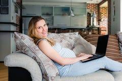 Gravid kvinna som vilar på soffan och arbete på bärbara datorn arkivbild