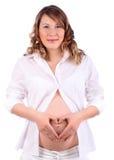 Gravid kvinna visar hjärta räcker by på buk Royaltyfri Fotografi