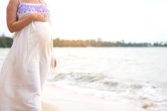 Gravid kvinnaanseende på strandhanden som trycker på på hennes buk royaltyfri bild