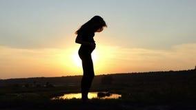 Gravid kvinnadans på solnedgången i ultrarapid stock video