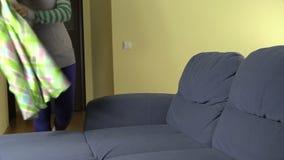 Gravid kvinnaflickan sitter på soffan och räkningen med plädet lager videofilmer