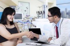 Gravid kvinnahandshaking med doktorn fotografering för bildbyråer