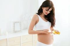 Gravid kvinnahudomsorg Kvinnlig applicerande olja på buken royaltyfri bild