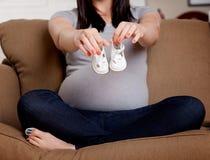 Gravid kvinnainnehavet behandla som ett barn skor Royaltyfria Bilder