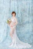 Gravid kvinnainnehavet blommar och att stå i budoarklänningen på en blå bakgrund Fotografering för Bildbyråer