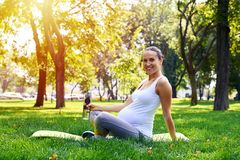 Gravid kvinnainnehavflaska av vatten, sammanträde på yoga som är matt i p Royaltyfria Foton