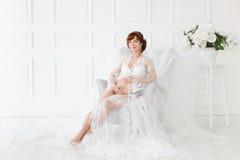 Gravid kvinnasammanträde i en stol i en härlig vit klänningbudoar Royaltyfri Fotografi