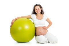 Gravid kvinnasammanträde med den gymnastiska bollen Royaltyfria Bilder