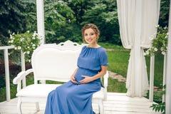 Gravid kvinnasammanträde på en bänk royaltyfria foton