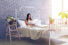 Gravid kvinnasammanträde på säng med bärbara datorn och att ha frukosten Royaltyfri Fotografi