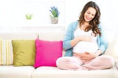 Gravid kvinnasammanträde på en soffa Fotografering för Bildbyråer