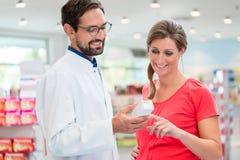 Gravid kvinnashopping i apotek Arkivbild