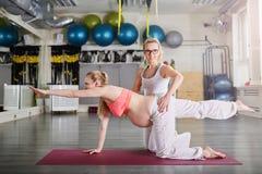 Gravid kvinnautbildningsyoga som säkras av den personliga instruktören Fotografering för Bildbyråer
