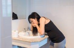 Gravid kvinnlig kväljning in i handfatet på wc:n, kvinna med morgonsjukdom arkivfoto