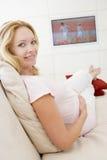 gravid le hållande ögonen på kvinna för television Royaltyfri Bild