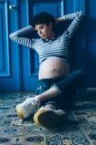 Gravid le kvinna som sitter på trägolv i rum maternity motherhood royaltyfri bild