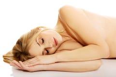Gravid le kvinna som vilar på golvet Arkivfoto