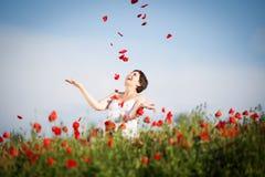 Gravid lycklig kvinna i ett blomningvallmofält Royaltyfria Foton
