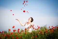 Gravid lycklig kvinna i ett blomningvallmofält Royaltyfri Foto