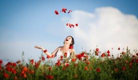 Gravid lycklig kvinna i ett blomningvallmofält Arkivfoton