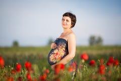 Gravid lycklig kvinna i ett blomningvallmofält fotografering för bildbyråer