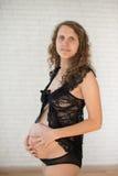 Gravid lyckligt le kvinnasammanträde på en soffa Royaltyfri Bild