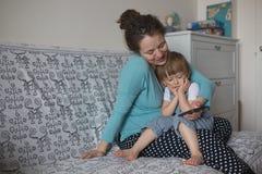 Gravid mamma- och sonlitet barn som spelar med telefonen, livsstil rea royaltyfria bilder