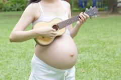 Gravid mamma som spelar ukulelet Arkivbilder