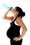Gravid modelldricksvatten efter hennes genomkörare för fysisk kondition royaltyfria bilder