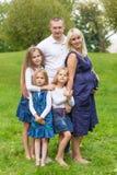 Gravid moder för barn med hennes familj i en parkera Arkivbild
