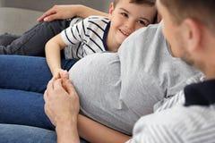 Gravid moder, fader och son som tillsammans spenderar tid på soffan hemma royaltyfria foton