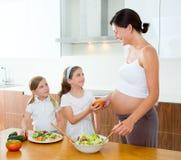 Gravid moder med henne döttrar på kök arkivbilder