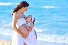 Gravid moder och dotter på stranden Royaltyfri Fotografi