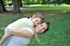 Gravid moder och dotter som har gyckel Arkivfoton