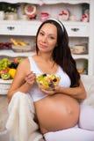 Gravid moder som äter fruktsallad Kvinnahälsa, bantar och näring Vitaminer och havandeskap Arkivfoto