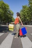 Gravid på övergångsstället med shoppingpåsar Royaltyfria Bilder