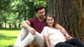 Gravid parsammanträde parkerar in och att le in i kamera, lyckligt moderskap som uppfostrar royaltyfria bilder