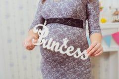 gravid s kvinna för buk Plätera prinsessan i händerna av en gravid kvinna Arkivbild