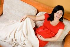 gravid sittande kvinna för härlig soffa arkivfoto