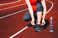 Gravid sportig kvinna som snör åt gymnastikskor på sportstadion Royaltyfri Foto