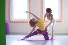 Gravid ung kvinna för rött huvud på yogagrupp med instruktören royaltyfria foton