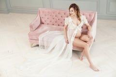 Gravid ung kvinna i vit klänningpeignoir som sitter på den rosa soffan och att visa hennes nakna buk och härliga ben som bort ser arkivbilder