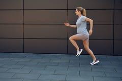 Gravid ung kvinna som håller färdigt sprinta royaltyfria foton