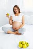 Gravid ung kvinna som rymmer Apple, medan sitta på sängen Hea Arkivfoto