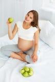 Gravid ung kvinna som rymmer Apple, medan sitta på sängen Hea Royaltyfri Foto