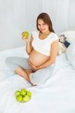 Gravid ung kvinna som rymmer Apple, medan sitta på sängen Hea Arkivbilder
