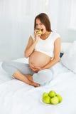 Gravid ung kvinna som rymmer Apple, medan sitta på sängen Hea Royaltyfri Bild