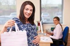 Gravida affärskvinnaGoing On Maternity tjänstledigheter från kontor royaltyfria foton